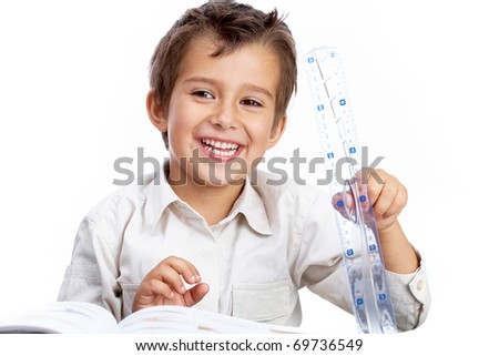 Portrait of a little schoolboy holding a ruler, looking at camera and smiling - stock photo