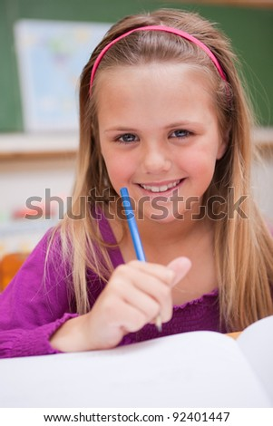 Portrait of a little schoolgirl writing on a book in a classroom - stock photo