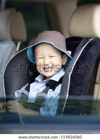 Portrait of a little smiling asian boy in the car