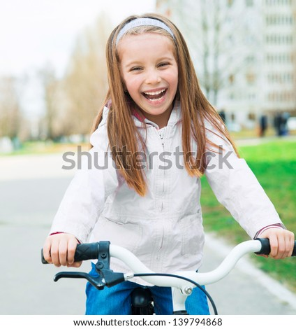 Portrait of a little smiling girl on a bicycle in summer park outdoors - stock photo