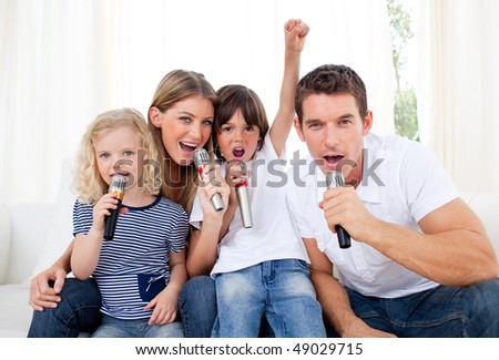 Portrait of a lively family singing through microphone in the living room