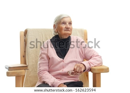 Portrait of a lonely elderly woman sitting in a fotel - stock photo