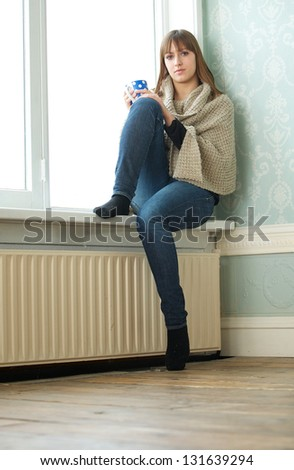 Portrait of a lonely girl sitting in empty room - stock photo