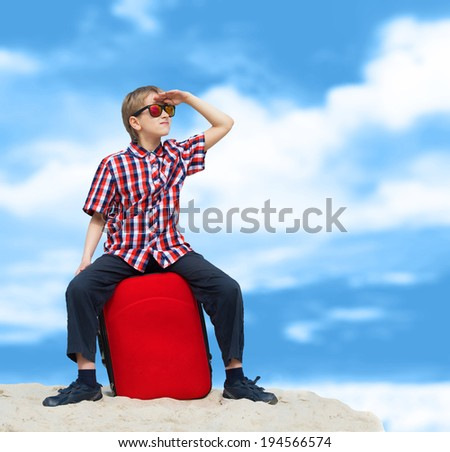 Portrait of a lost boy with his luggage, tropical beach background - stock photo
