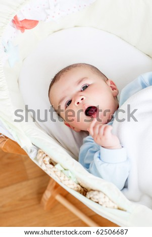 Portrait of a lovely baby lying in his cradle at home - stock photo