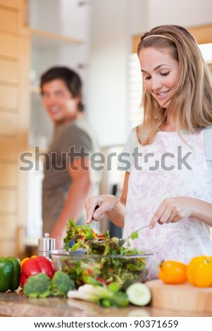 Portrait of a lovely couple making a salad in their kitchen
