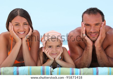 Portrait of a lovely family at the beach - stock photo