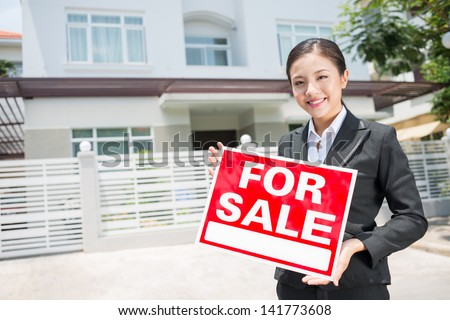 Portrait of a lovely female broker with a placard in hands - stock photo