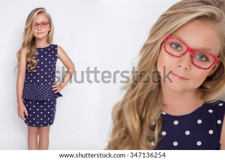 Portrait of a lovely little girl daughter in long blond hair and violet, blue dress with white dots and red glasses with white dots looks at the camera, photo on the white background amazing eyes