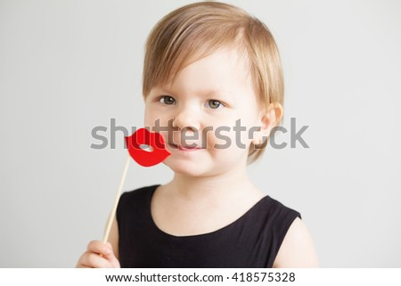 Portrait of a lovely little girl with funny red paper lips against a white background - stock photo