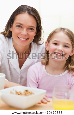 Portrait of a lovely mother and her daughter having breakfast in a kitchen - stock photo