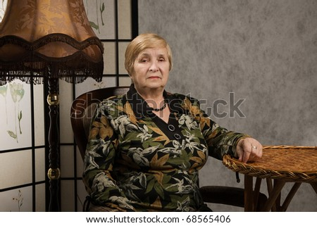 Portrait of a lovely old woman in a vintage style interior
