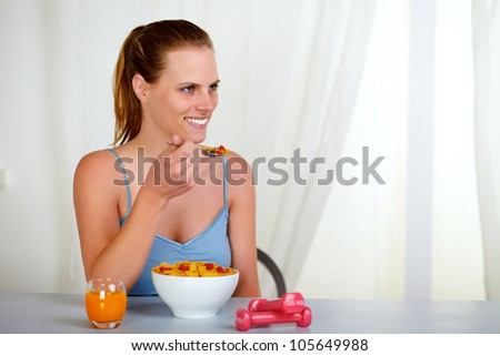Portrait of a lovely pretty woman smiling and eating at home indoor - stock photo