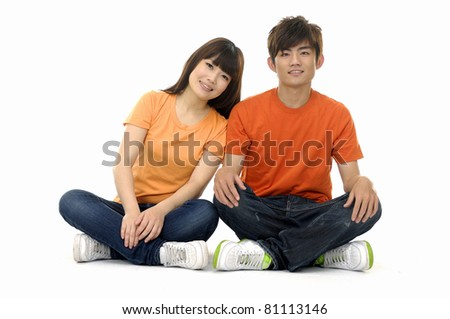 Portrait of a lovely smiling young couple relaxing on the floor - stock photo