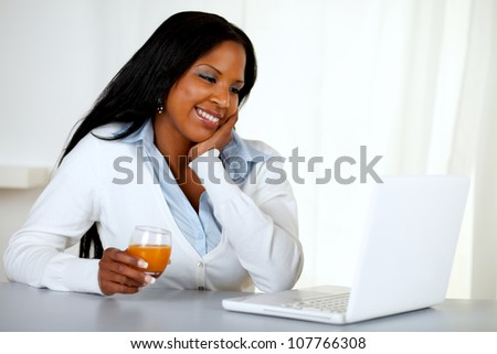 Portrait of a lovely student girl smiling and looking to laptop at soft colors composition - stock photo