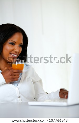 Portrait of a lovely student girl smiling and looking to laptop screen while drinking a healthy orange juice at soft colors composition - stock photo