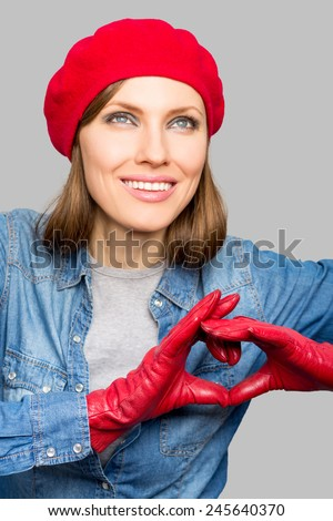 Portrait of a lovely woman making heart of fingers - stock photo