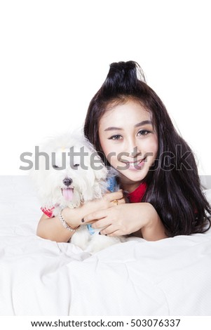 Portrait of a lovely woman with hugging a puppy while lying and smiling in front of camera, isolated on the background
