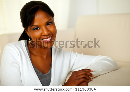 Portrait of a lovely young female smiling and looking at you while sitting on couch. With Copyspace - stock photo