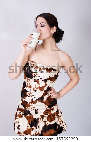 portrait of a lovely young lady having a glass of milk - stock photo