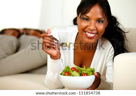 Portrait of a lovely young lady lying on a sofa and eating a vegetable salad while looking at you - stock photo
