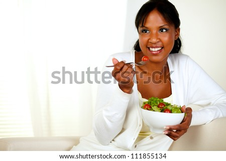 Portrait of a lovely young woman enjoying fresh vegetable salad. With copyspace. - stock photo