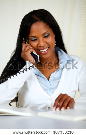 Portrait of a lovely young woman on phone at home indoor while is studying - stock photo