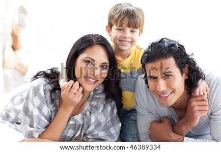 Portrait of a loving family lying on the floor against a white background