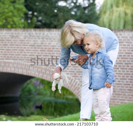 Portrait of a loving grandmother standing outdoors with little girl - stock photo