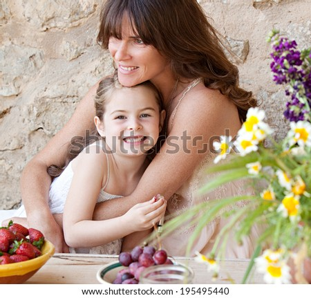 Portrait of a loving mother and young daughter sitting together at a holiday home table outdoors eating fresh fruits and enjoying a summer vacation, hugging. Family fun, travel and lifestyle. - stock photo