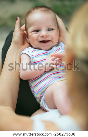 Portrait of a loving mother holding her cute, laughing baby with gorgeous blue eyes on his back, in her lap in the garden - stock photo