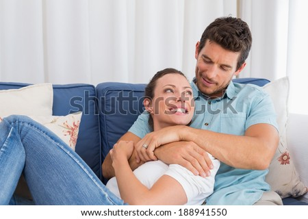 Portrait of a loving young couple sitting on couch at home - stock photo