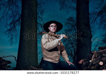 portrait of a lumberjack in the forest with an axe over the shoulder