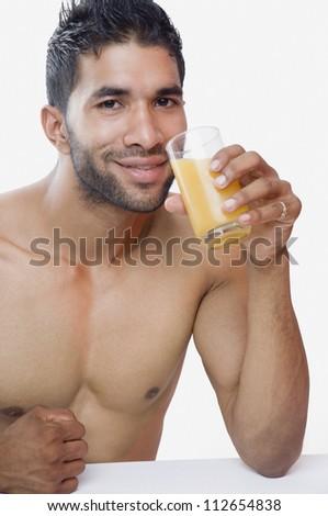 Portrait of a macho man drinking juice - stock photo
