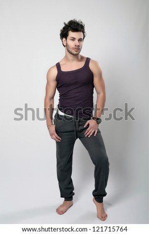 Portrait of a macho man holding jacket against grey background - stock photo