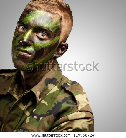 portrait of a mad soldier against a grey background - stock photo