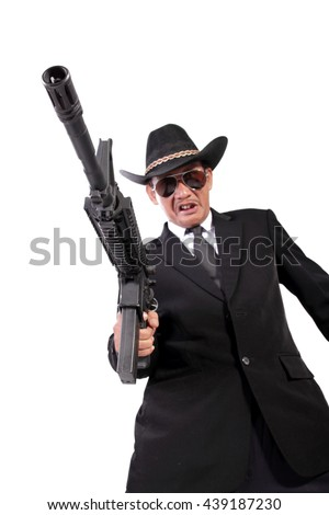 Portrait of a mafia with his pointed handgun, shot taken from low angle, isolated on white background - stock photo