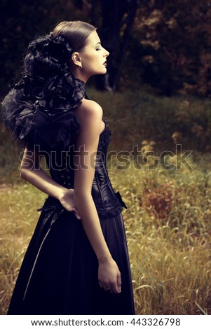 Portrait of a magnificent brunette woman wearing long black dress walking in a mystic forest. The old times, the Gothic style. Fashion.