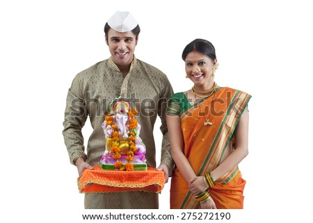 Portrait of a Maharashtrian couple with a Ganesh idol