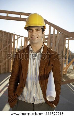 Portrait of a male architect standing with hands in pockets at construction site