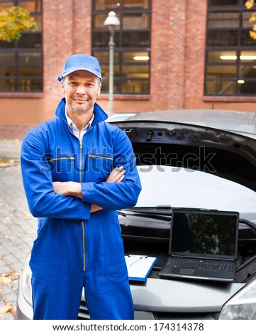 Portrait Of A Male Car Mechanic With Arm Crossed - stock photo