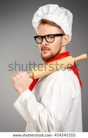 Portrait of a male chef cook in uniform holding plunger. Occupation. Studio shot.