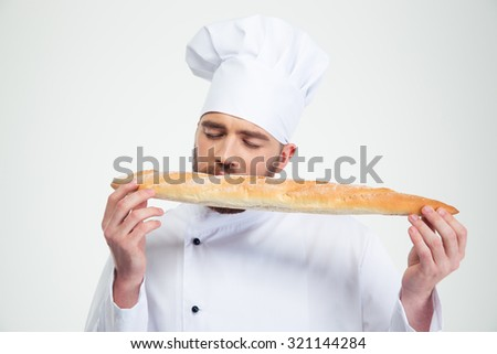 Portrait of a male chef cook smelling fresh bread against white background - stock photo