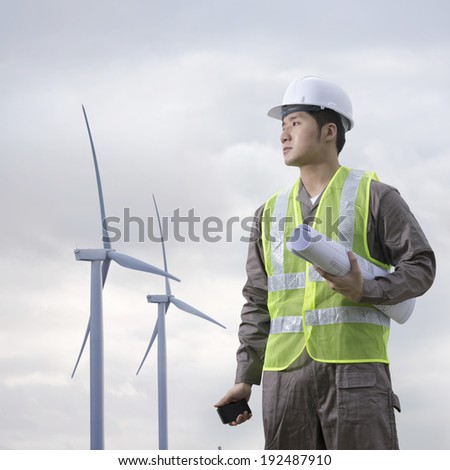 Portrait of a male Chinese industrial engineer at work checking winturbines - stock photo