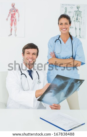 Portrait of a male doctor and female surgeon examining x-ray in a medical office - stock photo