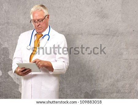 Portrait Of A Male Doctor Holding A Tab, Background - stock photo