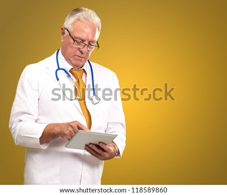 Portrait Of A Male Doctor Holding A Tab On A Yellow Background - stock photo