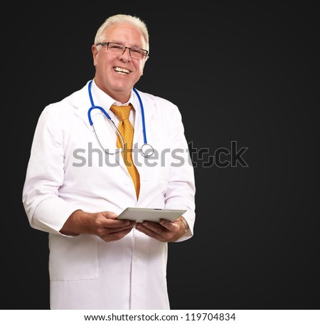 Portrait Of A Male Doctor Holding A Tab On Black Background - stock photo