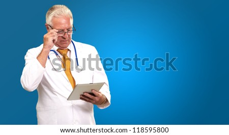 Portrait Of A Male Doctor Holding A Tab On Blue Background - stock photo