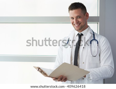 Portrait of a male doctor holding his patient chart in bright modern hospital - stock photo